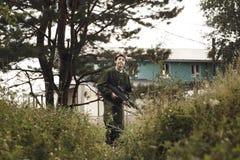 Muchacho joven en el camuflaje con un arma, lasertag Fotos de archivo libres de regalías