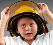 Muchacho joven en el casco del bombero Fotografía de archivo libre de regalías