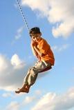 Muchacho joven en el oscilación Foto de archivo libre de regalías