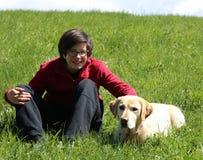 muchacho joven en el prado en las montañas con su Labrado amarillo Foto de archivo