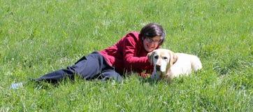 Muchacho joven en el prado en las montañas con su perro de Labrador Fotografía de archivo libre de regalías