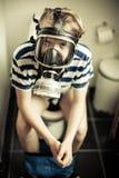 Muchacho joven en la careta antigás del retrete que lleva Fotos de archivo