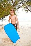 Muchacho joven en la playa con resaca Fotografía de archivo libre de regalías