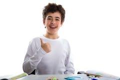 Muchacho joven en la preparación que sonríe y que muestra la muestra del éxito Imagen de archivo libre de regalías