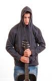 Muchacho joven en la sudadera con capucha que coloca y que sostiene su guitarra Fotos de archivo libres de regalías