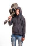 Muchacho joven en la sudadera con capucha que se coloca con su guitarra en el hombro Fotografía de archivo libre de regalías