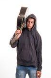 Muchacho joven en la sudadera con capucha que se coloca con su guitarra en el hombro Imagen de archivo libre de regalías