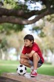 Muchacho joven en la tabla con la bola Imagenes de archivo