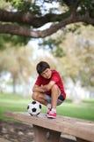 Muchacho joven en la tabla con la bola Foto de archivo libre de regalías