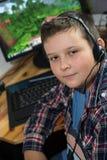 Muchacho joven en las auriculares que juegan al juego de la PC Fotos de archivo libres de regalías