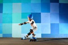 Muchacho joven en los pcteres de ruedas que hacen la diapositiva contra la pared azul de la pintada Fotografía de archivo