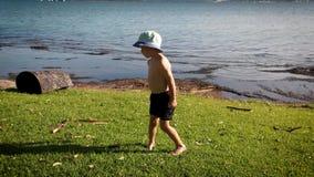 Muchacho joven en pantalones cortos y sombrero del cubo en la orilla herbosa de un lago en la altura del verano que muestra su ve metrajes
