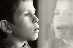Muchacho joven en pensamiento con la reflexión de la ventana Foto de archivo libre de regalías