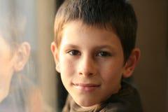 Muchacho joven en pensamiento con la reflexión de la ventana imagen de archivo