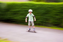 Muchacho joven en su tablero del patín fotos de archivo libres de regalías