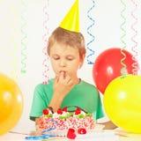 Muchacho joven en torta de cumpleaños festiva de la prueba del sombrero Imagen de archivo