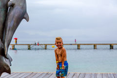Muchacho joven en un embarcadero por el océano por una estatua del delfín Fotografía de archivo libre de regalías