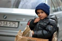 Muchacho joven en una caja en Baku, capital de Azerbaijan, al lado de BMW Fotografía de archivo libre de regalías