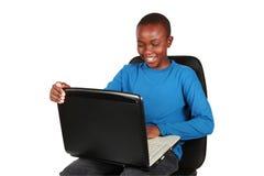 Muchacho joven en una computadora portátil Fotografía de archivo libre de regalías