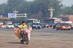 Muchacho joven en una e-bici para la entrega de la flor, Pekín, China Imagen de archivo