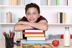 Muchacho joven en una pila de libros en la escuela Fotos de archivo