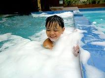 Muchacho joven en una piscina con las burbujas Imagenes de archivo