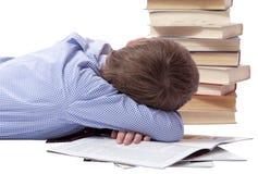 Muchacho joven en vestido clásico que duerme con el montón de libros foto de archivo libre de regalías