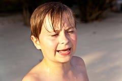 Muchacho joven enojado con la cara mojada en Imagen de archivo