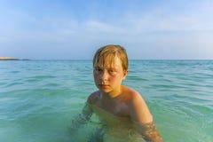 Muchacho joven enojado en el océano hermoso Foto de archivo