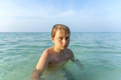 Muchacho joven enojado que camina en el océano en la playa Imágenes de archivo libres de regalías
