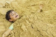 Muchacho joven enterrado en arena foto de archivo