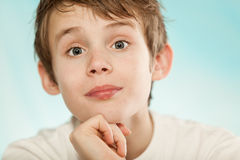 Muchacho joven escéptico que aumenta sus cejas Fotografía de archivo