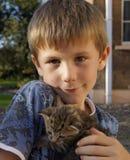 Muchacho joven feliz con el gatito joven del animal doméstico Imagen de archivo