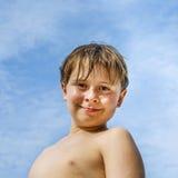 Muchacho joven feliz con el pelo y los ojos marrones en la playa Imágenes de archivo libres de regalías