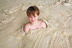 Muchacho joven feliz cubierto por la arena fina Fotos de archivo