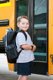 Muchacho joven feliz delante del autobús escolar Imagenes de archivo