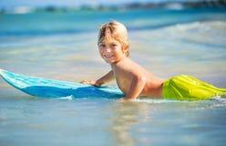 Muchacho joven feliz en el océano en la tabla hawaiana Imágenes de archivo libres de regalías