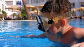 Muchacho joven feliz en la m?scara que se zambulle que se relaja en piscina de agua azul en el hotel de Egipto almacen de metraje de vídeo