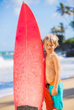 Muchacho joven feliz en la playa con la tabla hawaiana Fotos de archivo libres de regalías