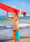 Muchacho joven feliz en la playa con la tabla hawaiana Imagen de archivo