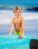 Muchacho joven feliz en la playa con la tabla hawaiana Foto de archivo