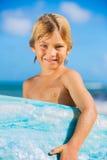 Muchacho joven feliz en la playa con la tabla hawaiana Fotografía de archivo libre de regalías