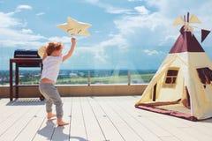Muchacho joven feliz, ni?o que juega cerca de la tienda de la tienda india de la materia textil en el patio del verano foto de archivo