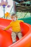 Muchacho joven feliz que desliza abajo la diapositiva y que se divierte Foto de archivo