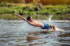 Muchacho joven feliz que disfruta de nadar en el río durante vacaciones de verano Felicidad y concepto feliz de la niñez Fotos de archivo