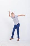 Muchacho joven feliz que salta en el fondo blanco Fotos de archivo libres de regalías