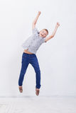 Muchacho joven feliz que salta en el fondo blanco Imagen de archivo