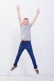 Muchacho joven feliz que salta en el fondo blanco Imágenes de archivo libres de regalías