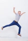 Muchacho joven feliz que salta en el fondo blanco Foto de archivo libre de regalías
