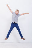 Muchacho joven feliz que salta en el fondo blanco Imagen de archivo libre de regalías